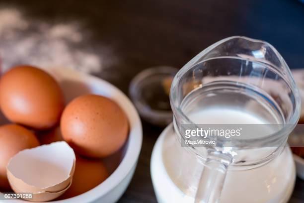 ingredientes para fazer panquecas ou bolo - farinha, ovos, manteiga, leite no fundo de madeira velho. vista superior. estilo rústico ou rural. - table top - fotografias e filmes do acervo
