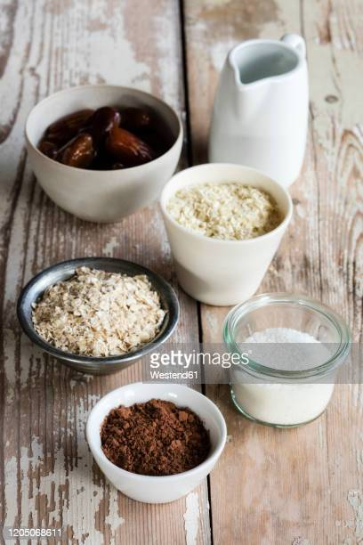 ingredients for making protein balls (coconut oil, dates, millet flakes, oat flakes, grated coconut and cocoa powder) - millet stock pictures, royalty-free photos & images
