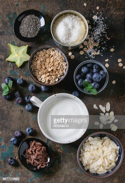 Ingredients for making smoothie for healthy breakfast Bowls of yogurt blueberries granola almond chia seeds coconut milk chocolate mint carambola...