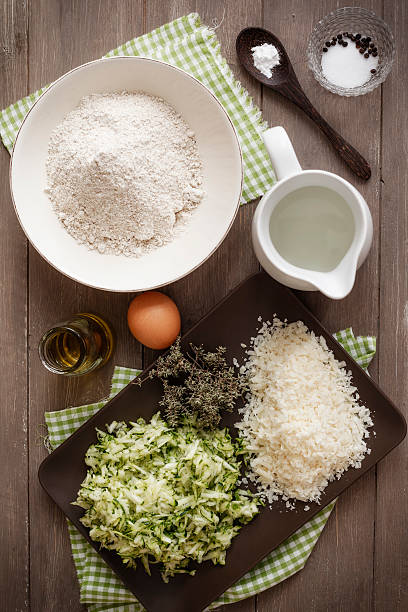 Ingredients for making zucchini muffins on table
