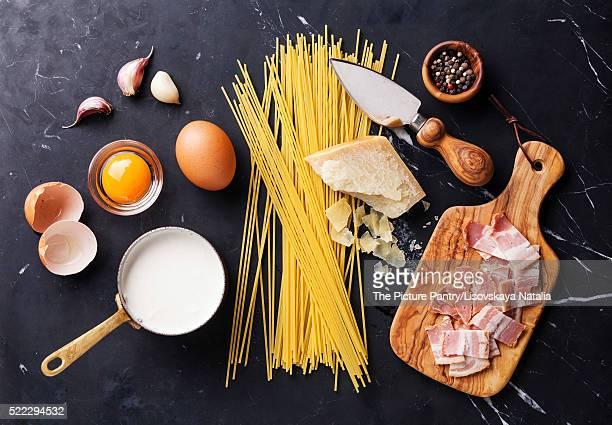 Ingredients for Pasta Carbonara on dark marble background