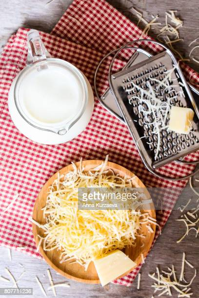 ingredients for pasta cheese sauce or pizza, freshly grated parmesan or cheddar hard cheese, raw milk in a pot, kitchen tools, grater, wooden plate and kitchen towel, rustic vintage style, top view - table top - fotografias e filmes do acervo
