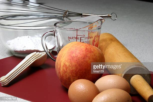 Ingredientes para melocotón zapatero remendón. Huevos, harina, recipiente para medir, palo de amasar.