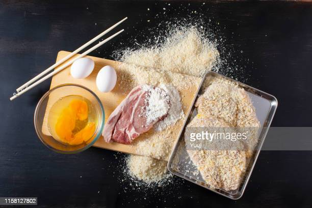 ingredients for pork cutlet. eggs, bread crumbs, flour and pork placed on a cutting board. - tonkatsu imagens e fotografias de stock