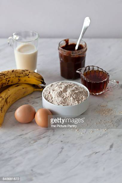 Ingredients for vegan banana bread with chocolate hazelnut spread on the white marble surface