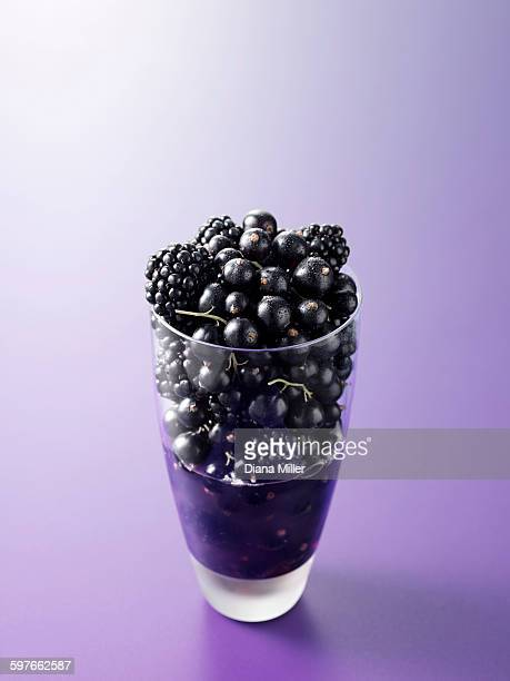 Ingredients in drinking glass for blackcurrant and blackberry fruit juice