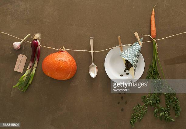 Ingredients of Hokkaido soup hanging on clothesline in front of brown background