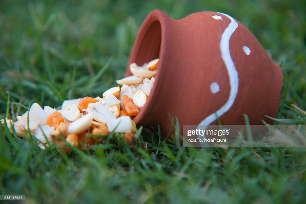 Ingredients spilling out of earthen pot : Stock Photo