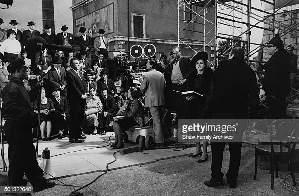 Ingrid Bergman and Anthony Quinn and a crowd of onlookers with the crew and director Bernhard Wicki in 1963 during the filming of The Visit in Rome...