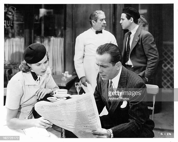 Ingrid Bergman and Humphrey Bogart looking at newspaper in restaurant in a scene from the film 'Casablanca' 1942