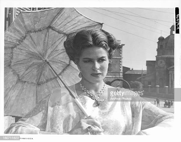 Ingrid Bergman holding sun umbrella in a scene from the film 'The Visit' 1964