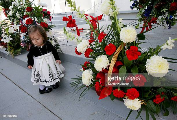 Ingrid Freeman months looks over a display of flowers at the funeral of her father Captain Brian Freeman during a memorial service at Ft Rosecrans...