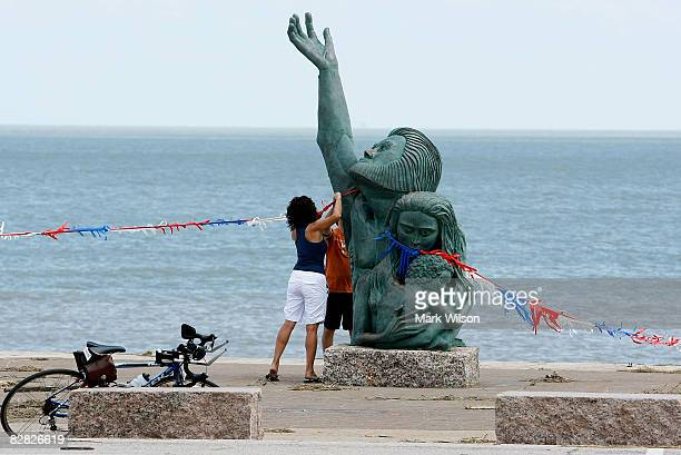 Ingrid Gonzalez hangs a ribbon on the sculpture that commemorates the 1900 Hurricane that killed over 6000 people before a prayer vigil September 15...