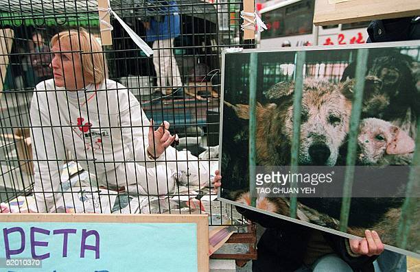 Ingrid Newkirk the president of the People of the Ethical Treatment of Animals cages herself at a night market in downtown Taipei 22 March in protest...
