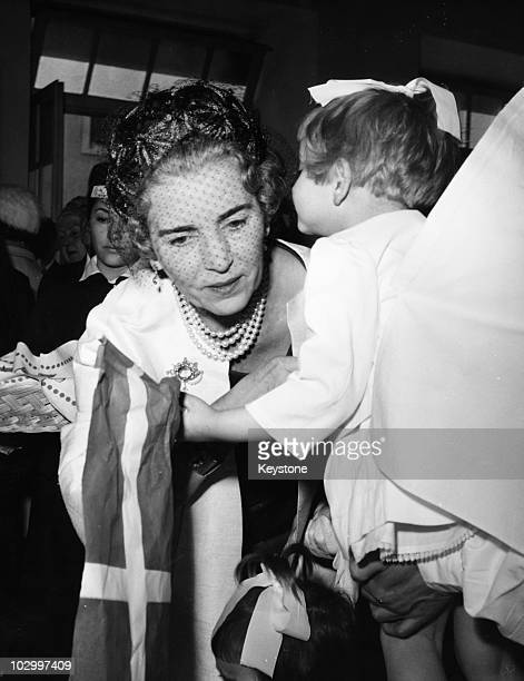 Ingrid of Denmark queen consort of King Frederick IX of Denmark receiving a kiss from a little girl holding a Danish flag at the Italian Red Cross...
