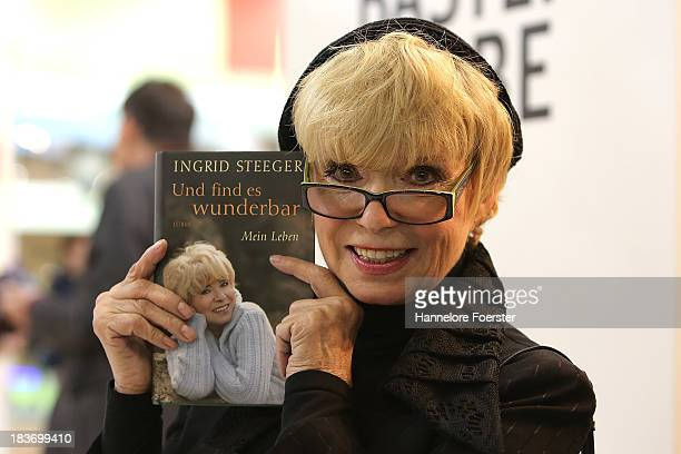 Ingrid Steeger, actor, poses with a copy of her biography, at the Frankfurt Book Fair, on October 9, 2013 in Frankfurt am Main, Germany. This year's...