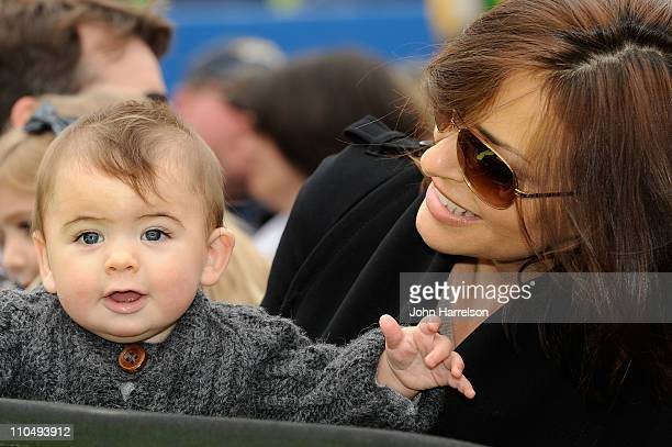 Ingrid Vandebosch holds her son Leo Benjamin by the Pepsi Max Chevrolet driven by her husband Jeff Gordon prior to the NASCAR Sprint Cup Series Jeff...