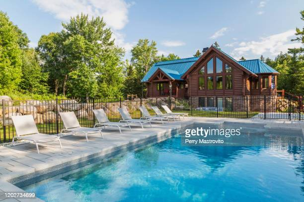 in-ground salt water swimming pool and brown stained milled eastern white pine timber and flat log profile home facade with stone cladding on walk-out lower level and blue standing-seam sheet metal roof, quebec, canada - eastern white pine stock pictures, royalty-free photos & images