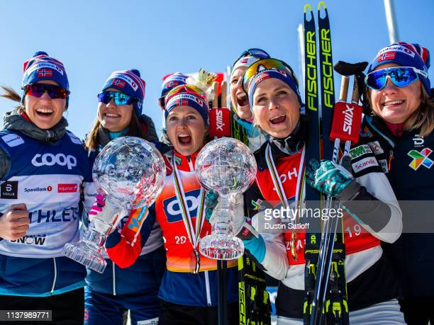 Ingvild Flugstad Oestberg of Norway and Therese Johaug of Norway pose with the overall crystal globe and distance crystal globe after the podium...