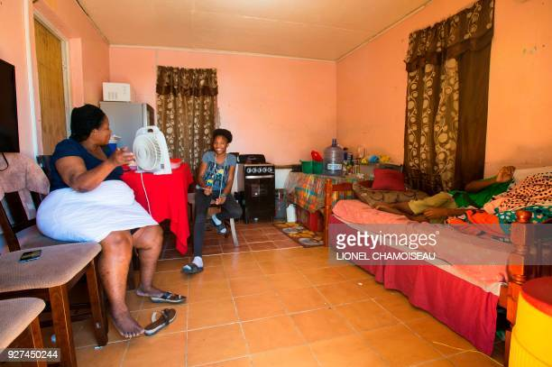 Inhabitant Josephine who lives with her 6 grand children in the remaining part of their house after living in a tent sits next to two of her grand...