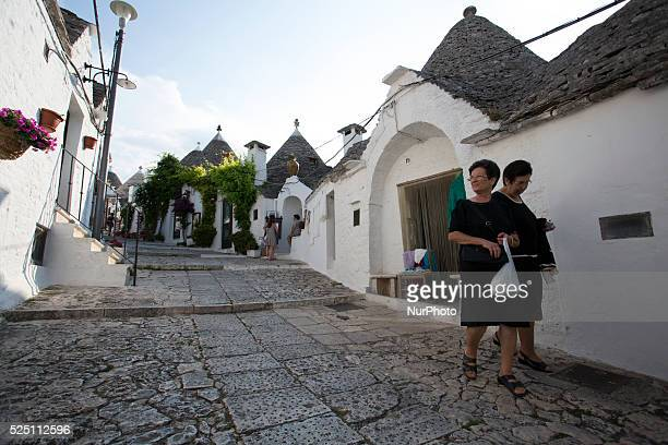 Inhabitant of Alberobello walk through a street in Alberobello on Aug 5 2014 Alberobello is a town in south east part of Italy in the Bari province...