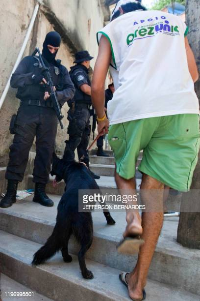 A inhabitant of Morro do Alemao shantytown passes by policemen on November 29 2010 in Rio de Janeiro Brazil Police scoured the sewers under Rio's...