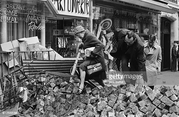 Inhabitants climb over piles of paving stones in the streets during the French student demonstrations in May 1968