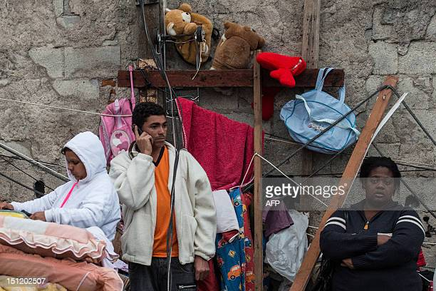 Inhabitants of a favela stand amidst some belongings following a fire in their place in the neighborhood of Congonhas airport in Sao Paulo Brazil on...