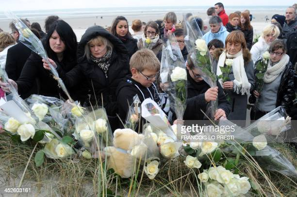 """Inhabitants of Berck-sur-Mer, Northern France lay bouquets of flowers as they take part on November 30, 2013 to a """"white march"""" in homage to the girl..."""