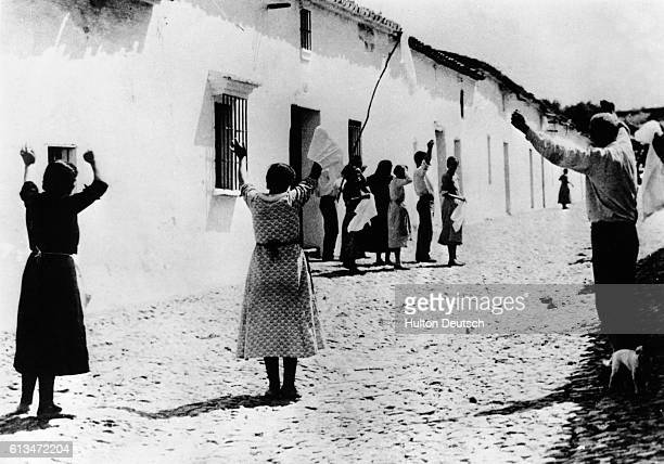 Inhabitants of Castilblanco de Los Arroyos raise their arms in gestures of surrender as Nationalist troops move into their village during the Spanish...