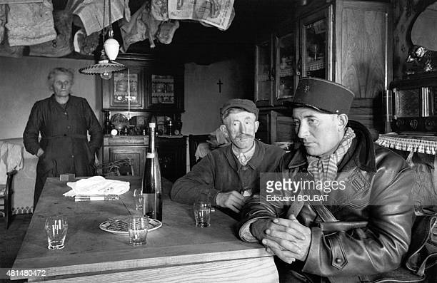 Inhabitants of Cheylade sharing a glass of brandy with the postman in the Cantal France