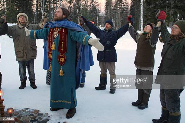 Inhabitants of Sun City in eastern Siberia pray March 2, 2002 in the morning with Vissaron, a religious cult figure who claims that he is the...