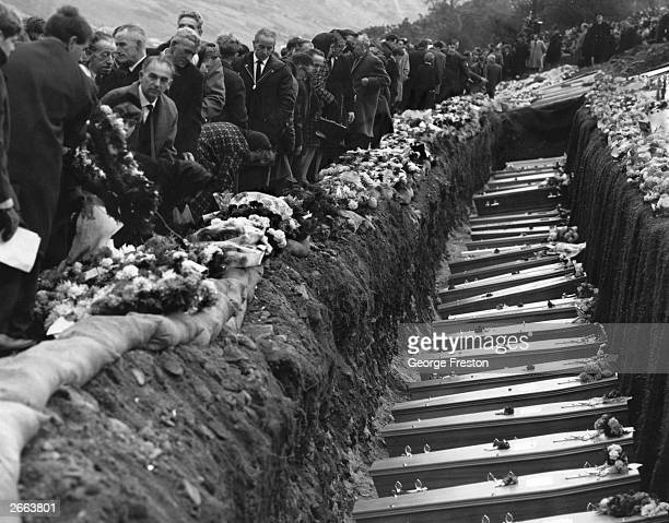 Inhabitants of the Welsh mining village of Aberfan attend the mass funeral for 81 of the 190 children and adults who perished when a landslide...