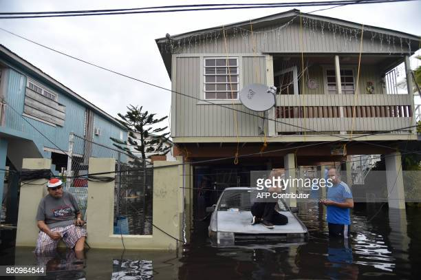 TOPSHOT Inhabitants stand in flood water in front of a house flooded in Juana Matos Catano Puerto Rico on September 21 2017 Puerto Rico braced for...