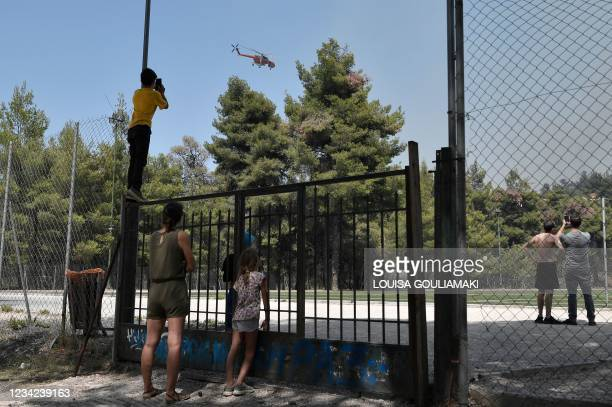 Inhabitants take pictures as a helicopter flies over a forest fire in Dionysos, north east of Athens, on July 27, 2021.