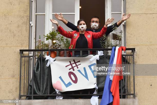 "Inhabitants wearing protective masks applaud at 20:00 from their balcony decorated with French flag and a banner with words: ""Love"" to show their..."