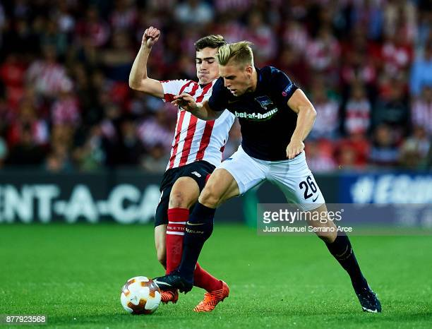 Inigo Cordoba of Athletic Club duels for the ball with Arne Maier of Hertha BSC during the UEFA Europa League group J match between Athletic Bilbao...