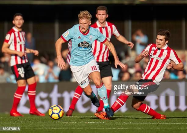 Inigo Cordoba of Athletic de Bilbao competes for the ball with Daniel Wass of Celta de Vigo during the La Liga match between Celta de Vigo and...