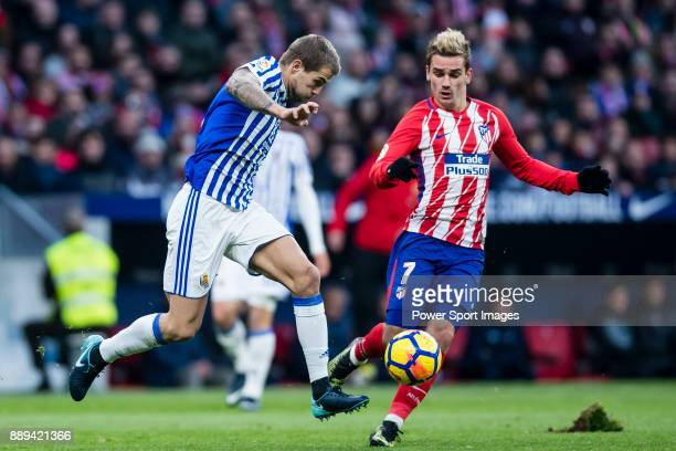 Inigo Martinez Berridi of Real Sociedad fights for the ball with Antoine Griezmann of Atletico de Madrid during the La Liga 201718 match between...