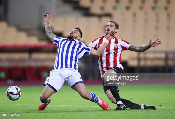 Inigo Martinez of Athletic Bilbao tackles Portu of Real Sociedad which leads to a penalty decision and a red card which was then overturned to a...