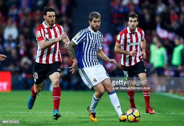 Inigo Martinez of Real Sociedad competes for the ball with Aritz Aduriz of Athletic Club during the La Liga match between Athletic Club Bilbao and...