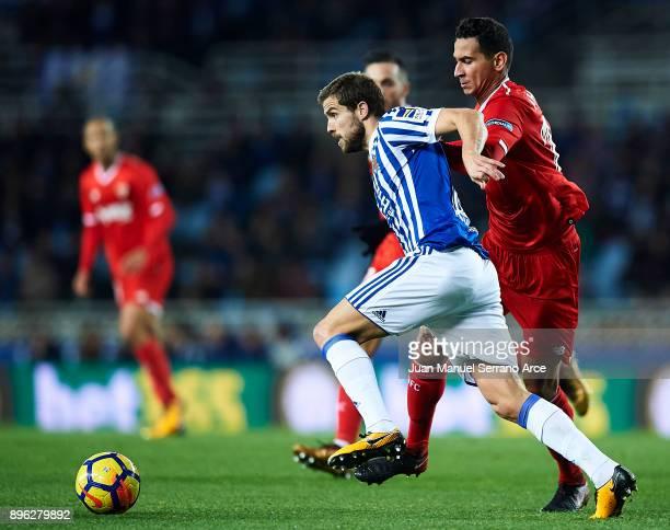 Inigo Martinez of Real Sociedad competes for the ball with Paulo Henrique Ganso of Sevilla FC during the La Liga match between Real Sociedad and...