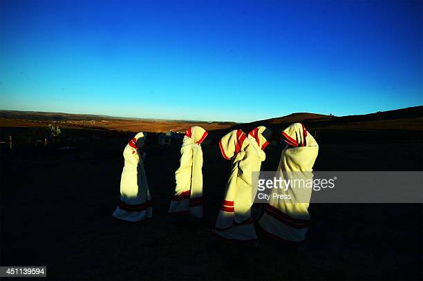 Initiates are smeared with white clay on their face and are covered in red and white blankets on June 20, 2014 in Ngunjana Village, South Africa. The...