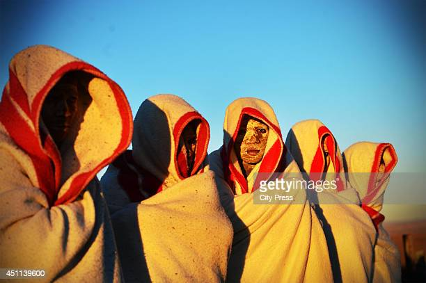 Initiates are smeared with white clay on their face and are covered in red and white blankets on June 20 2014 in Ngunjana Village South Africa The...