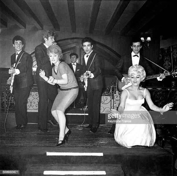 Initiation au twist avec la chanteuse Claire Ferval accompagnée des Chaussettes Noires dans un club parisien à Paris, France, le 21 novembre 1961.