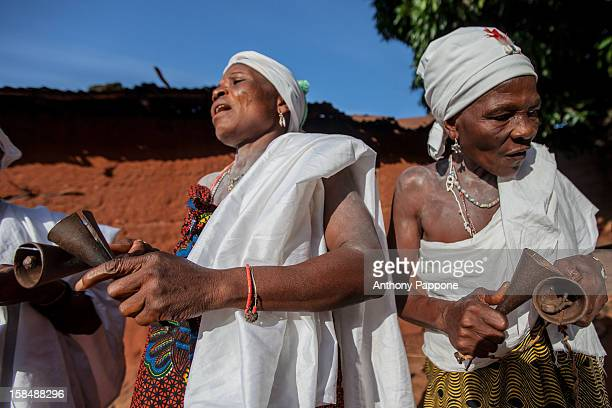 Initiation voodoo women sing and ring the bells in the traditional the sacred wood of Ahémé lake. Benin