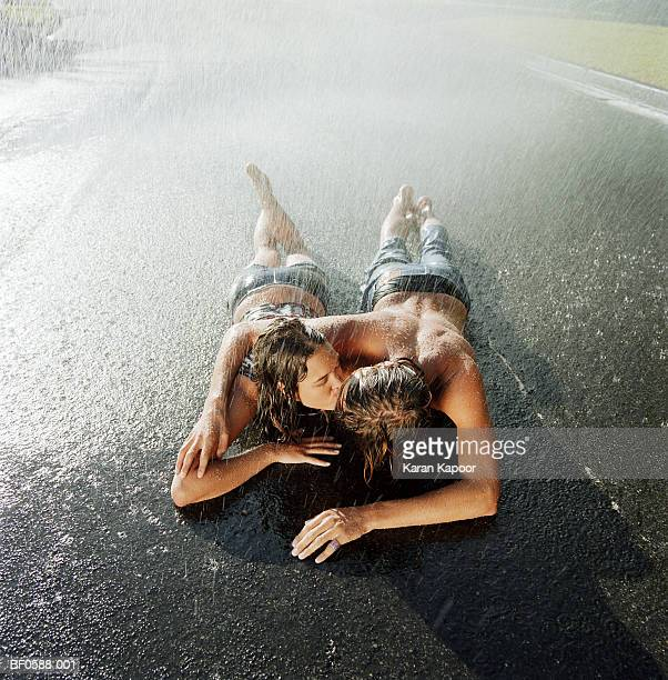 Initimate young couple lying on road in rain