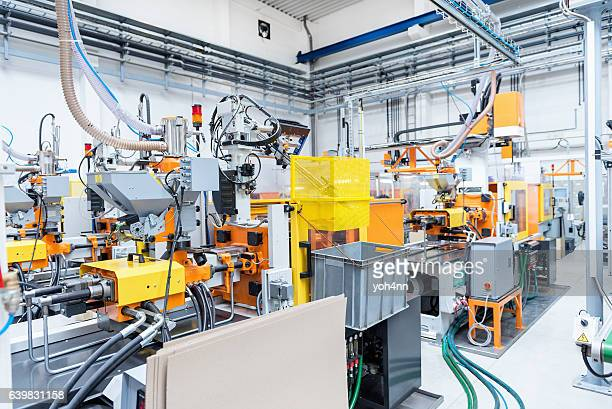 injection moulding machines inside of plastic factory - contraptie stockfoto's en -beelden