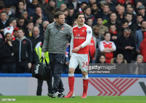 Injured Arsenal defender Hector Bellerin is led from the pitch by physio Colin Lewin during the Premier League match between Chelsea and Arsenal at...