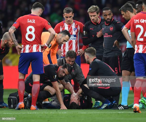 Injured Arsenal defender Laurent Koscielny is treated by physio Colin Lewin as Granto Xhaka looks on during the UEFA Europa League Semi Final second...